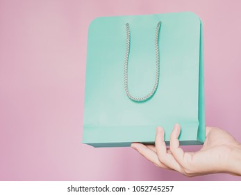 business ,finance and shopping concept from man hand hold green pastel paper shopping bag by right hand with pink pastel isolated background