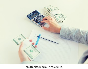 business, finance, tax and people concept - close up of woman hands counting us dollar money with calculator
