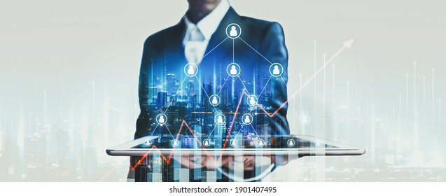 Business finance technology concept, Professional business man using tablet on network city and mlm digital marketing people graphic at night in Bangkok, Thailand