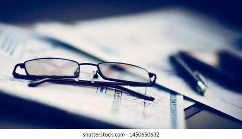 Business Financial Analysis workplace, glasses lie on documents
