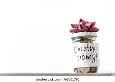 Business financial concept, coins in glass jar with the word Christmas money saving white background
