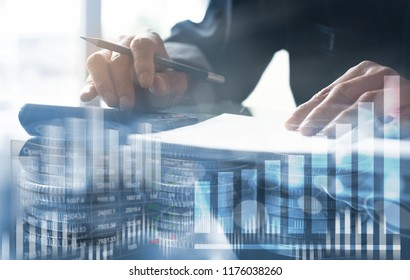 Business and financial concept. Double exposure of Businessman working investment project, using calculator to calculate business data at modern office, coins with stock exchanges graphics  interface.