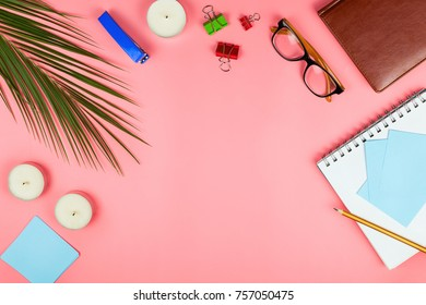 Business flatlay with glasses, palm leaf, candles, stapler, pen, notebook, colorful clipper and paper notes. Concept of a woman's work place. Flat lay. Pink background. Copyspace