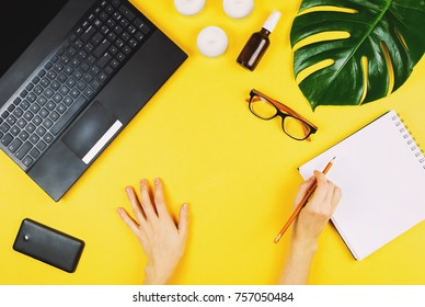 Business flatlay on yellow with laptop, mobile phone, glasses, philodendron leaf, candles, cream and woman's hands holding pen. Concept of a freelancer work place.