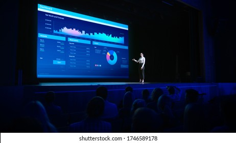 Business Forum Economics Conference Stage: Visionary Female Chief Analyst Delivers Speech and Shows Infographics, Statistics on Movie Theater Screen. Presentation with Speaker in Full Auditorium Hall