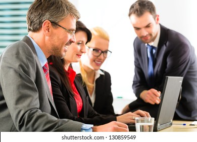 Business - Four professionals in office in business attire looking at laptop screen working together