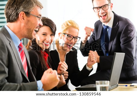 Business - Four professionals in office in business attire looking at laptop screen working together, they rejoice