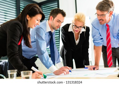 Business - Four professionals in the office in business clothes when planning a strategy for the future of the business