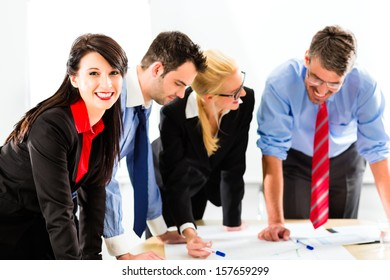 Business - Four professionals in the office in business clothes when planning a strategy for the future of the business, a woman smiles into the camera