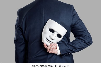 Business fraud concept. Businessman hide the mask in hand behind his back.