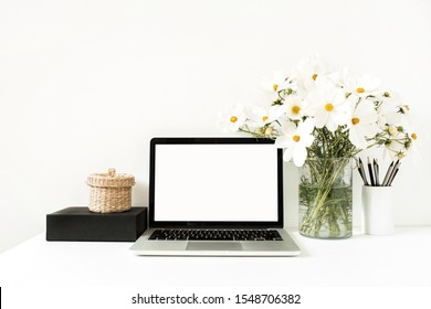 Business, freelance, blogger concept. Mock up, empty, copy space. Laptop standing on white table against white wall with daisies in vase, black box, straw basket.