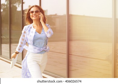 Business and freelance concepts. Close-up portrait of executive working with a mobile phone in the street with office buildings in the background.