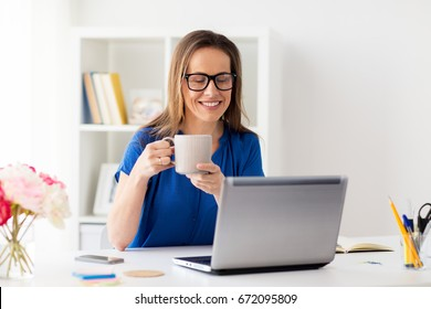business, freelance, people and technology concept - happy smiling woman with laptop computer drinking coffee at home or office