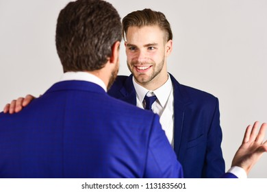 Business and friendship concept. Man with happy face in jacket listening his business partner. Successful negotiations between businessmen. Boss and employee speaking at meeting on light background.