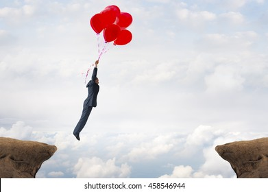 business gap concept businessman flying over a crevasse using helium balloons