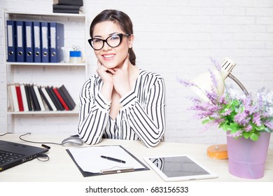 business girl in glasses sits in an Office at a computer folder paper