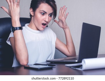 Business girl sits opposite the computer in gray tones. Emotional portrait of shock