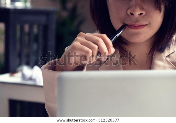 business girl thinking pointing pen on her mouse vintage tone