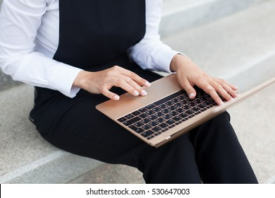 Business girl using laptop outdoors