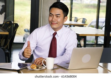Business is giving sign thumb up in while working with computer.