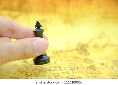 Business Global and planning concept. Close up of man hand holding black king chess piece and put down on vintage world map.
