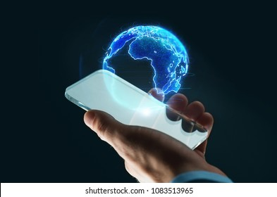 business, globalization and future technology concept - close up of businessman hand with transparent smartphone and earth hologram over black