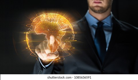business, globalization and future technology concept - close up of businessman with earth hologram over black