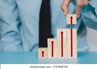 Business goal concept. Hand arranging higher arrow graph on wood cube block,Set target, Way to success, Improve profit and income.