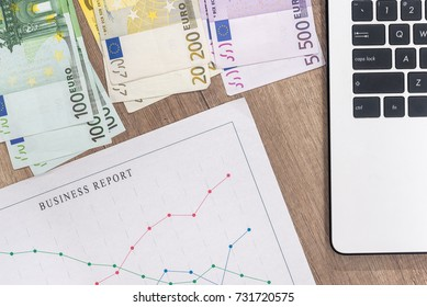 business graph with pen and laptop, euro banknote on desk