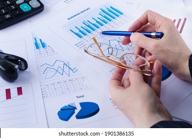 business graph, sales report, calculator, pen and glasses in a hands