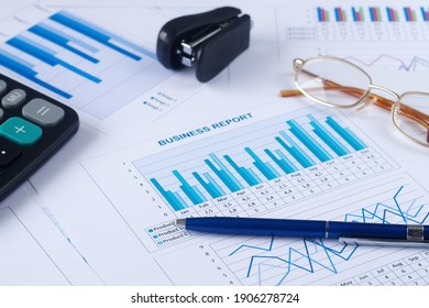 business graph, sales report, calculator, pen and glasses