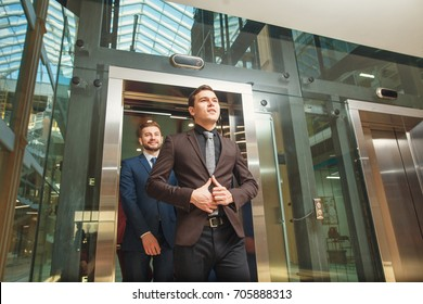 business group comes out from glass Elevator