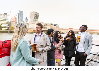 Business group in London drinking beer after work. They all are young, smiling and wearing smart casual clothes. Mixed race group. Also could refer to a group of friends.