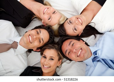 Business group lying on the floor with their heads together