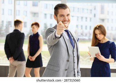 Business group with male leader pointing at the camera in foreground