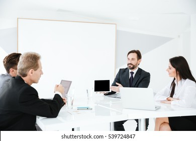 Business group sitting by the table in conference room with desk on background