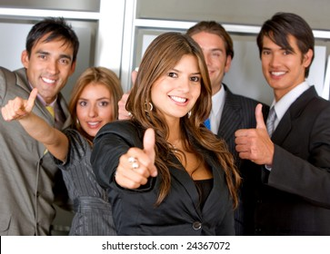 Business group standing in an office with thumbs up
