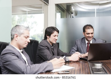 business group of three men in a business meeting