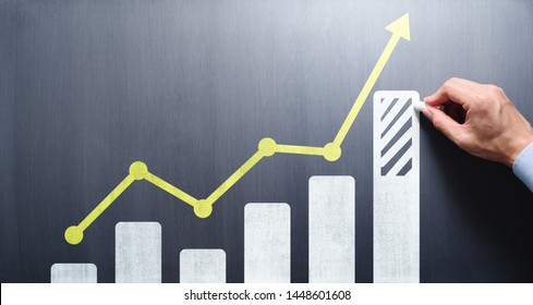 Business growth analysis and advice concept. Consultant drawing bar chart and line graph on chalkboard.