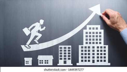 Business growth and career development plan. Business education. Businessman drawing office building and arrow on chalkboard.