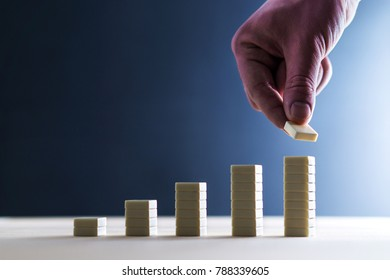 Business growth, financial success, record result or increase in turnover concept. Development, improvement and reaching goals. Angel investor making investment and taking risk. Hand stacking tiles.