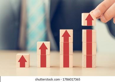 business growth go success progress process concept. business man hand arranging wooden cube block with grow up