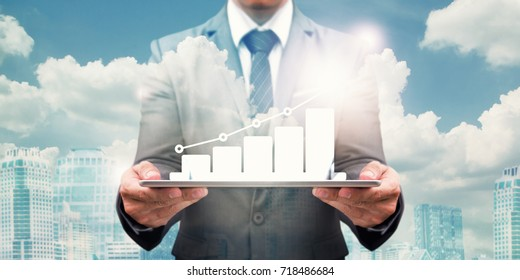 Business growth on digital tablet by business man over the cloudy and sky