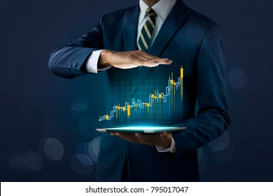 Business growth, progress or success concept. Businessman is showing a growing virtual hologram stock on dark tone background.
