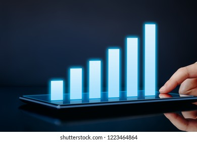 Business growth, success or development concept. Hand touching tablet showing a growing virtual hologram graph with copy space on dark background.