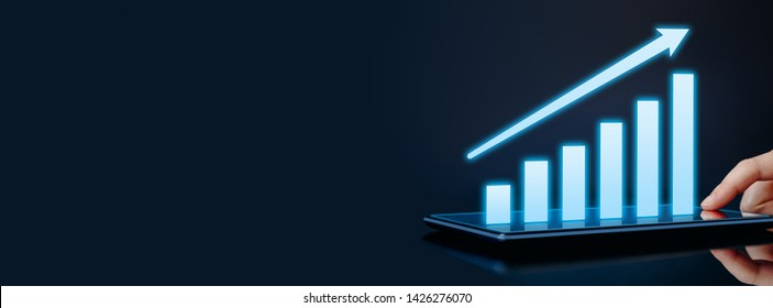 Business growth, success or development concept. Hand touching tablet showing a growing virtual hologram graph on dark background. Header banner template with copy space.