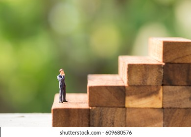Business, growth and Succession concept. Businessman miniature people figure standing and thinking on wood stair made from wooden blocks toy with green nature background.