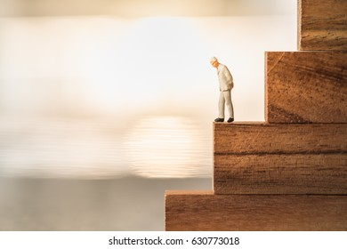 Business, growth and Succession concept. Businessman miniature figure standing and thinking on wood stair made from wooden blocks toy.