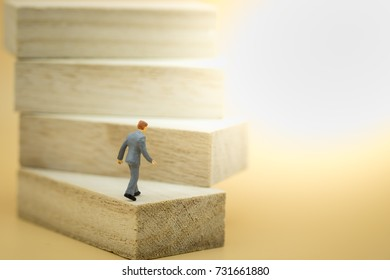 Business, growth and Succession concept. Businessman miniature figure walking to the top on wood stair made from wooden blocks toy.