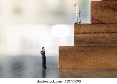 Business, growth and Succession concept.  Two businessman miniature figures standing, looking and thinking on wood stair made from wooden blocks toy.